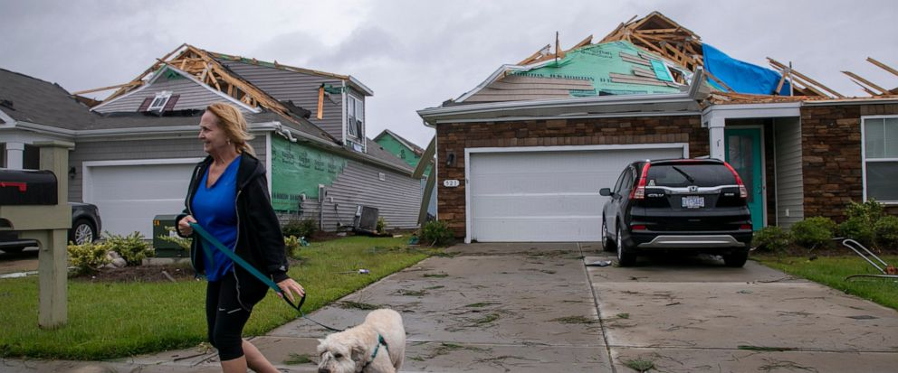 Kathy Desiderio took advantage of a calm between burst of rain to walk her dog Lily and survey the tornado damage at her neighbors homes. A tornado touched down in the The Farm at Brunswick County in Carolina Shores, N.C. on Thursday, Sept. 5, 2019,