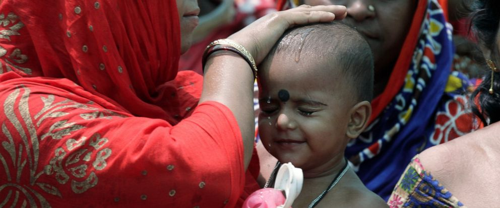 A woman wets the head of a child during an election rally addressed by Trinamool Congress leader and Chief Minister of West Bengal state Mamata Banerjee at Anchana in Mathurapur, about 60 kilometers south of Kolkata, India, Thursday, May 16, 2019. Wi