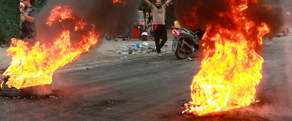 FILE - In this Sunday, Oct. 6, 2019 file photo, anti-government protesters set fires and close a street during a demonstration in Baghdad, Iraq. The protests have plunged the country into a new cycle of instability since last week, one that could pot