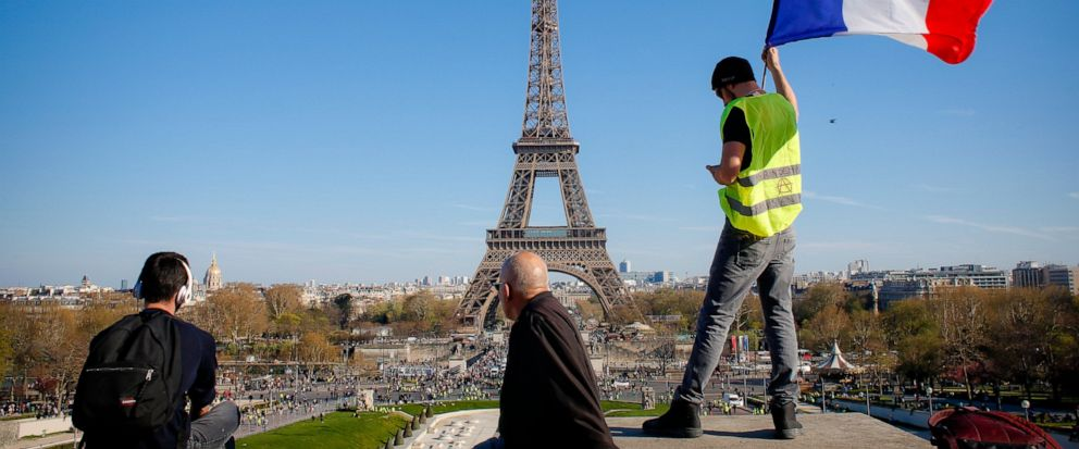 FILE - In this Saturday, March 30, 2019 file photo, a man holds a French flag as French with the Eiffel Tower in the background, during protests in Paris. Paris is wishing the Eiffel Tower a happy birthday with an elaborate laser show retracing the m