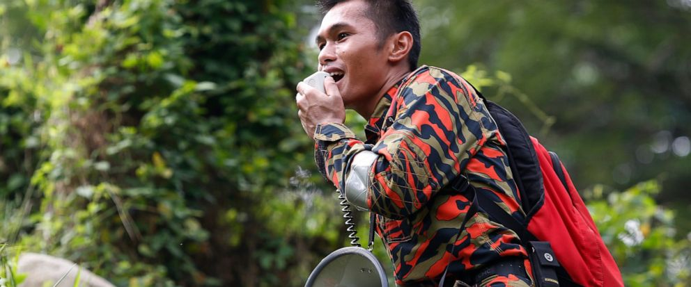 A member of a rescue team uses a loudspeaker as he conducts a search and rescue operation for a missing British girl at a forest in Seremban, Negeri Sembilan, Malaysia, Friday, Aug. 9, 2019. Police in Malaysia said on Thursday that they are using voi