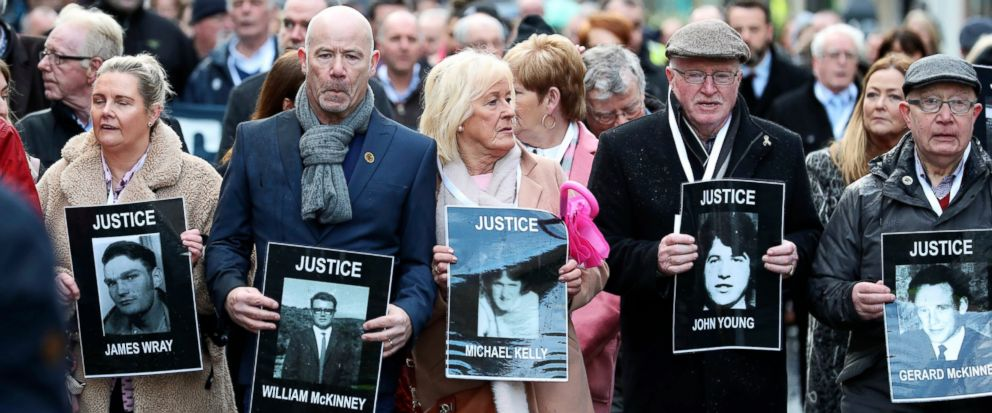 Families hold photographs of the victims of Bloody Sunday and march through the Bogside in Londonderry, Northern Ireland, Thursday March 14, 2019. A former British soldier is set to be prosecuted in connection with the deaths of two civil rights prot
