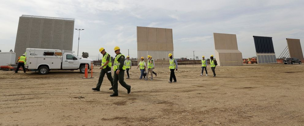 File - In this Oct. 19, 2017 file photo, people pass border wall prototypes as they stand near the border with Tijuana, Mexico, in San Diego. Montanas Senate president is proposing the state give more than $8 million to help build President Donald T