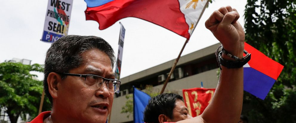 A protester raises his fist beside a national flag during a protest outside the Chinese Consulate in the financial district of Makati, metropolitan Manila, Philippines to mark Independence Day on Wednesday, June 12, 2019. The Philippine defense secre
