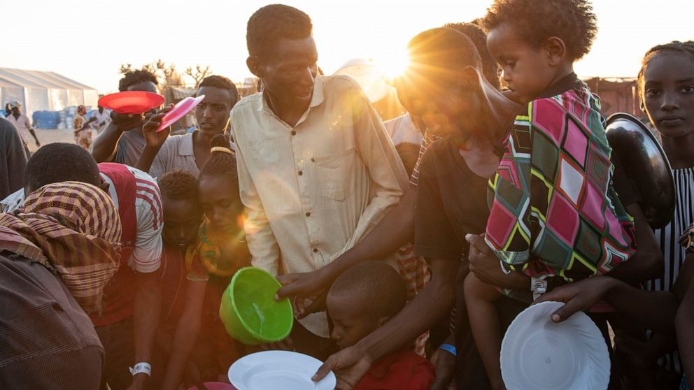 Tigray refugees who fled the conflict in Ethiopia's Tigray region, wait to get cooked rice served by Sudanese local volunteers at Um Rakuba refugee camp in Qadarif, eastern Sudan, Monday, Nov. 23, 2020. Ethiopia's government is again warning resident