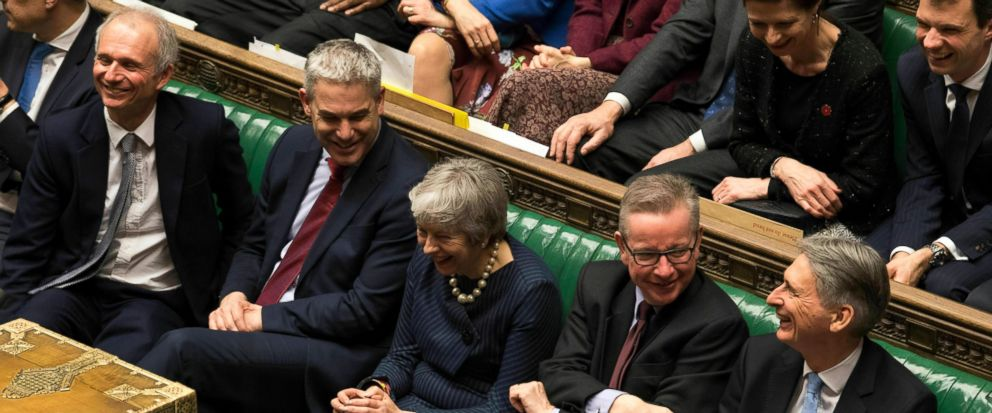 In this handout photo provided by UK Parliament, Britains Prime Minister Theresa May, centre, laughs during the Brexit debate in the House of Commons, London, Thursday March 14, 2019. Britains Parliament has voted to seek a delay of the countrys d