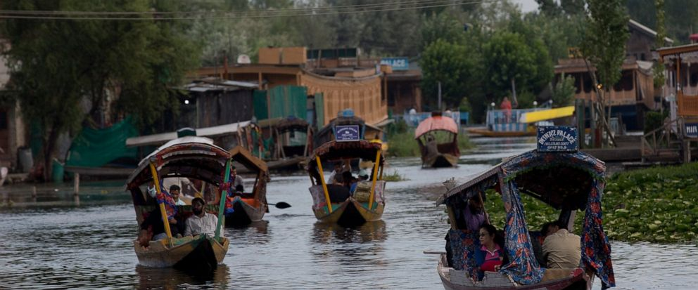 FILE - In this Saturday, Aug. 3, 2019, file photo, Tourists in Shikaras, a traditional gondola, cross the Dal Lake as they prepare to leave Srinagar, Indian controlled Kashmir. Authorities in Indian-controlled Kashmir are allowing tourists back into
