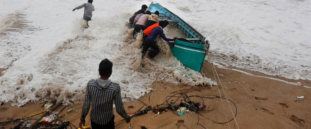 People try to move a fishing boat to a safer ground on the Arabian Sea coast in Veraval, Gujarat, India, Thursday, June 13, 2019. Authorities have evacuated nearly 300,000 people from Indias western coastline ahead of a very severe cyclone thats ex