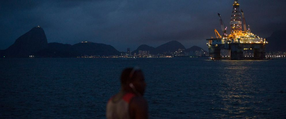 FILE - In this April 21, 2015 file photo, a man fishes near a floating oil platform in Guanabara Bay in Niteroi, Brazil. The administration of Jair Bolsonaro plans to auction seven oil fields despite contrary advice from analysts of Brazils main env