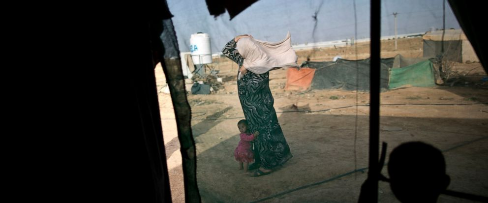 FILE -- In this June 3, 2016 file photo, a Syrian refugee holds on to her headscarf against the wind while she and her daughter stand outside their tent at an informal tented settlement near the Syrian border, on the outskirts of Mafraq, Jordan. Near