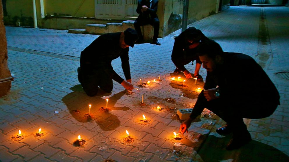 In this photo taken on Tuesday, Feb. 5, 2019, friends and relatives of Alaa Mashzoub light candles at his assassination site in Karbala, Iraq. Alaa Mashzoub, the Iraqi novelist who was gunned down this week in Karbala, was a secular civil society activist who used his bike to get around the Shiite holy city's infamous traffic and road closures. He was also an outspoken critic of foreign interferences in Iraqi affairs Iraq and political meddling by powerful militias backed by Iran. On Saturday, he was gunned down by unknown assailants who silenced him with 13 bullets as he rode his bicycle home for the last time. (AP Photo/Anmar Khalil)