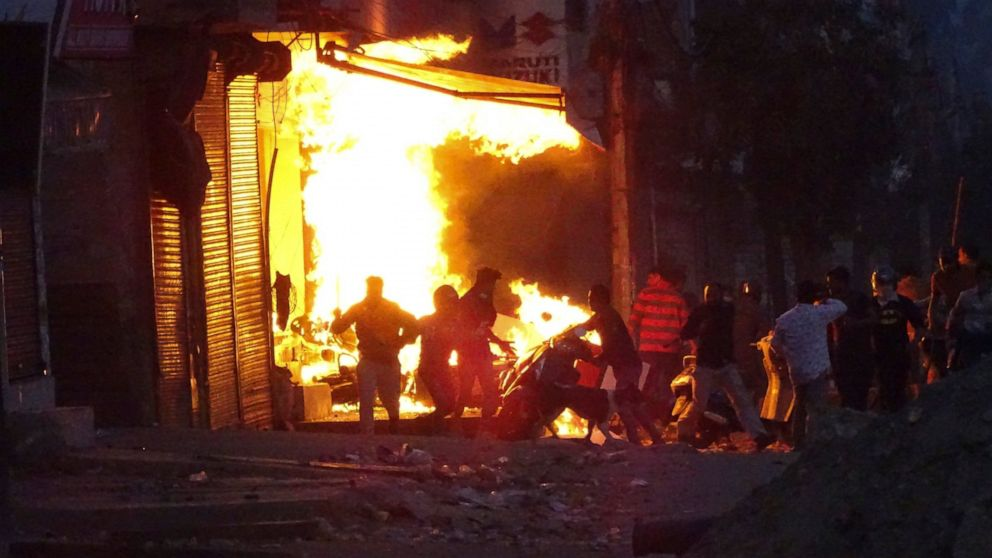 FILE - In this Tuesday, Feb. 25, 2020, file photo, a shop burns after it was set on fire by a mob in New Delhi, India. Indian police violated human rights during deadly religious riots in New Delhi earlier this year, Amnesty International said in a r