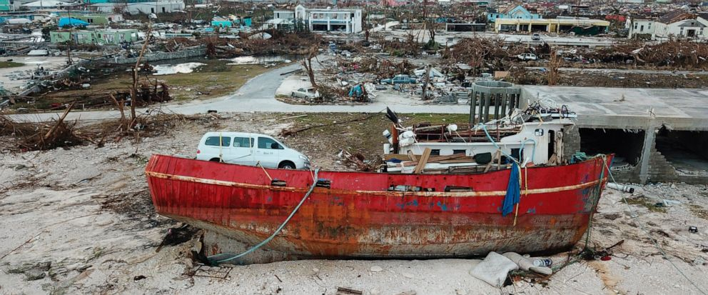 In this Sept. 6, 2019 photo, a boat sits grounded in the aftermath of Hurricane Dorian, in Marsh Harbor, Abaco Island, Bahamas. The Bahamian health ministry said helicopters and boats are on the way to help people in affected areas, though officials
