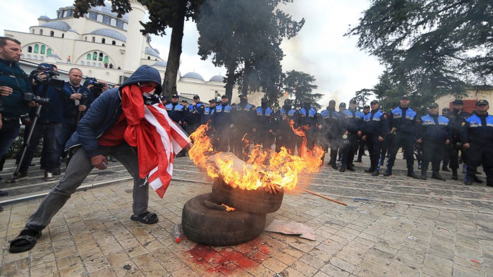 Protesters burn tyres outside the parliament building during an anti-government rally , in Tirana , Albania, Tuesday, March 5, 2019. Albania's opposition holds a rally calling for a new parliamentary election and accusing the government of corruption and links to organized crime. (AP Photo/ Hektor Pustina)