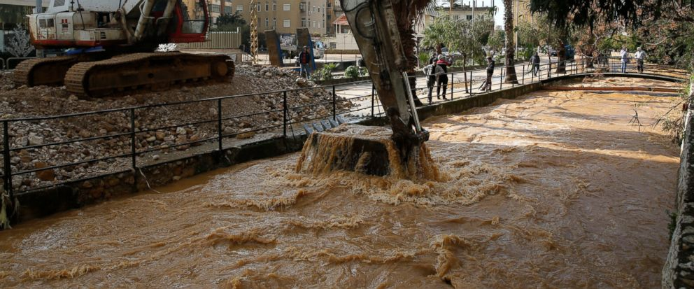 A Bulldozer cleans a river which overflowed, inundating cars and streets with muddy water and stones, in the town of Antelias, north of Beirut, Lebanon, Wednesday, Jan. 9, 2019. A storm packing snow and rain that has battered Lebanon for five days ha