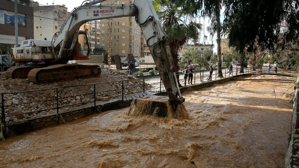 A Bulldozer cleans a river which overflowed, inundating cars and streets with muddy water and stones, in the town of Antelias, north of Beirut, Lebanon, Wednesday, Jan. 9, 2019. A storm packing snow and rain that has battered Lebanon for five days has left an 8-year-old Syrian girl dead, flooded neighborhoods and paralyzed major mountain roads. (AP Photo/Hussein Malla)