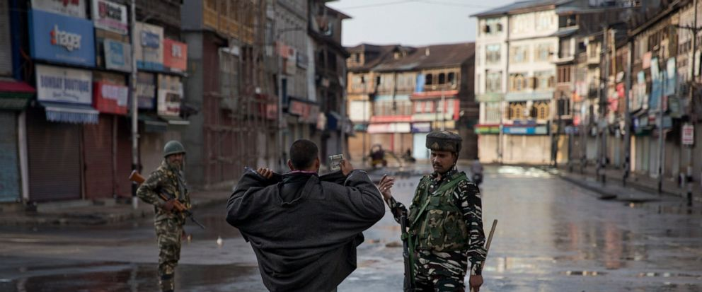 An Indian Paramilitary soldier orders a Kashmiri to lift his robe before frisking him during curfew in Srinagar, Indian controlled Kashmir, Thursday, Aug. 8, 2019. The lives of millions in Indias only Muslim-majority region have been upended since t