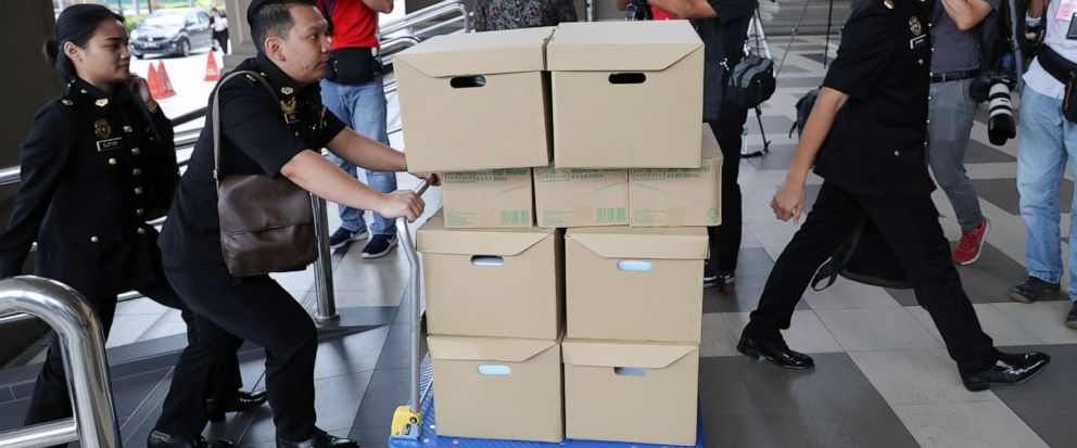 FILE - In this Wednesday, Aug. 28, 2019, file photo, Malaysian Anti-Corruption agencys staff transport documents for 1MDB case to Kuala Lumpur high court in Kuala Lumpur, Malaysia. Malaysia has ordered 80 people and groups to pay fines totaling abou