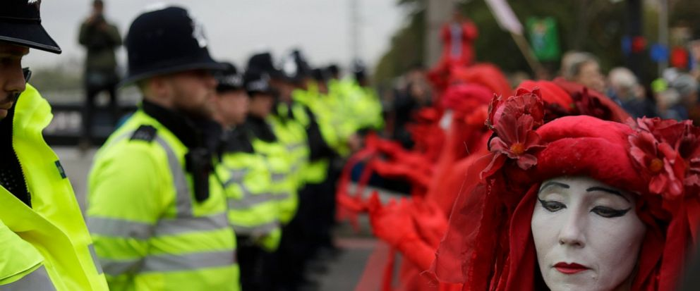 Environmental protestors face police on Lambeth bridge in central London Monday, Oct. 7, 2019. Environmental activists were set to block roads leading to Britains Parliament, rear, in an attempt to disrupt the heart of government. (AP Photo/Matt Dunham)