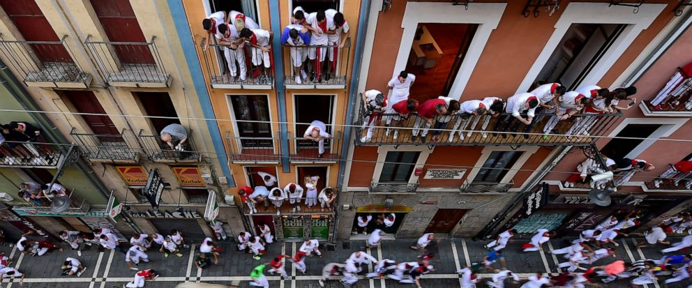 Revellers run next to fighting bulls during the running of the bulls at the San Fermin Festival, in Pamplona, northern Spain, Friday, July 12, 2019. Revellers from around the world flock to Pamplona every year to take part in the eight days of the ru