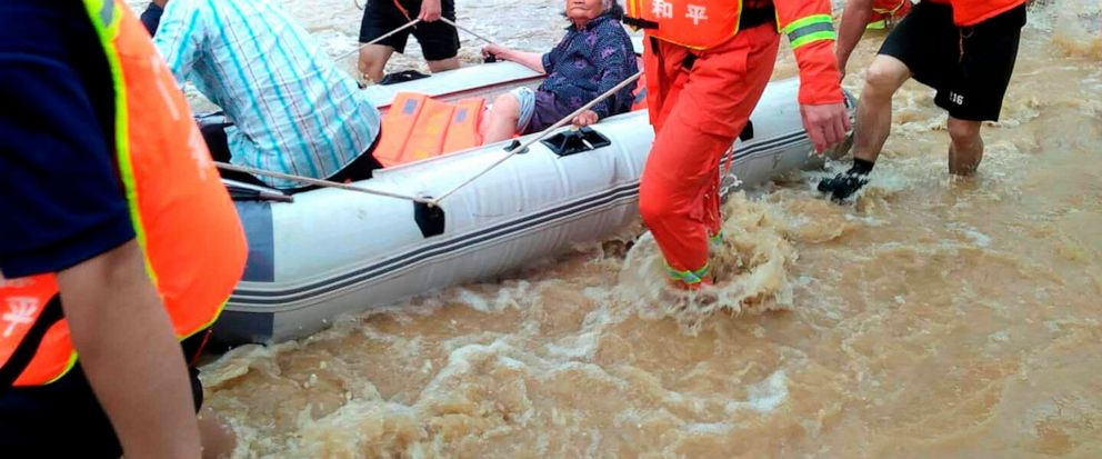 In this Monday, June 10, 2019, photo, rescuers evacuate an elderly woman on a boat in Heyuan in southern Chinas Guangdong province. Authorities say dozens of people have died and others are missing since heavy rainfall hit southern China in early Ju
