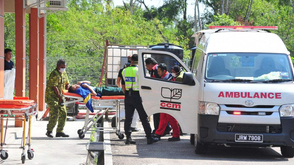 Emergency personnel unload a student from an ambulance after toxic chemical spill in Pasir Gudang, Johor state, on Wednesday, March 13, 2019. Malaysia's education ministry has ordered 34 schools to be closed in southern Johor state after toxic waste believed dumped in a river sickened dozens of students and teachers. (AP Photo/Thomas Yong)