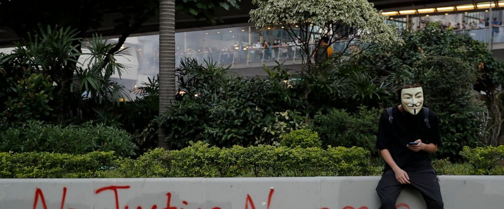 A masked protester sits near graffiti during a protest in Hong Kong, Friday, Oct. 4, 2019. Hong Kong Chief Executive Carrie Lam announced that protesters are banned from wearing masks to conceal their identities in a hardening of the governments sta