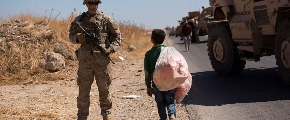 "A Syrian boy selling snacks looks at a U.S. soldier standing guard during the first joint ground patrol by American and Turkish forces in the so-called ""safe zone"" on the Syrian side of the border with Turkey, near Tal Abyad, Syria, Sunday, Sept. 8,"