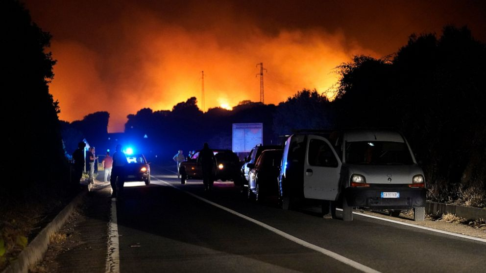 Cars are parked by the road as fires have been raging through the countryside in Cuglieri, near Oristano, Sardinia, Italy, early Sunday, July 25, 2021. Hundreds of people were evacuated from their homes in many small towns in the province of Oristano