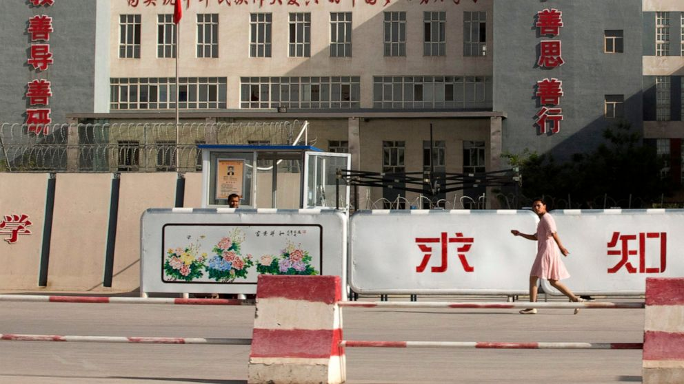 "FILE - In this Aug. 31, 2018, file photo, a woman walks past the Kashgar Dongcheng No. 4 Junior Middle School, which is part of a cluster of schools with slogans which read, ""Study hard to realize the Chinese dream of the great rejuvenation of the Ch"