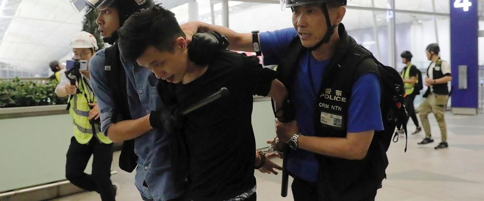 Policemen arrest a protester during a demonstration at the Airport in Hong Kong, Tuesday, Aug. 13, 2019. Chaos has broken out at Hong Kongs airport as riot police moved into the terminal to confront protesters who shut down operations at the busy tr