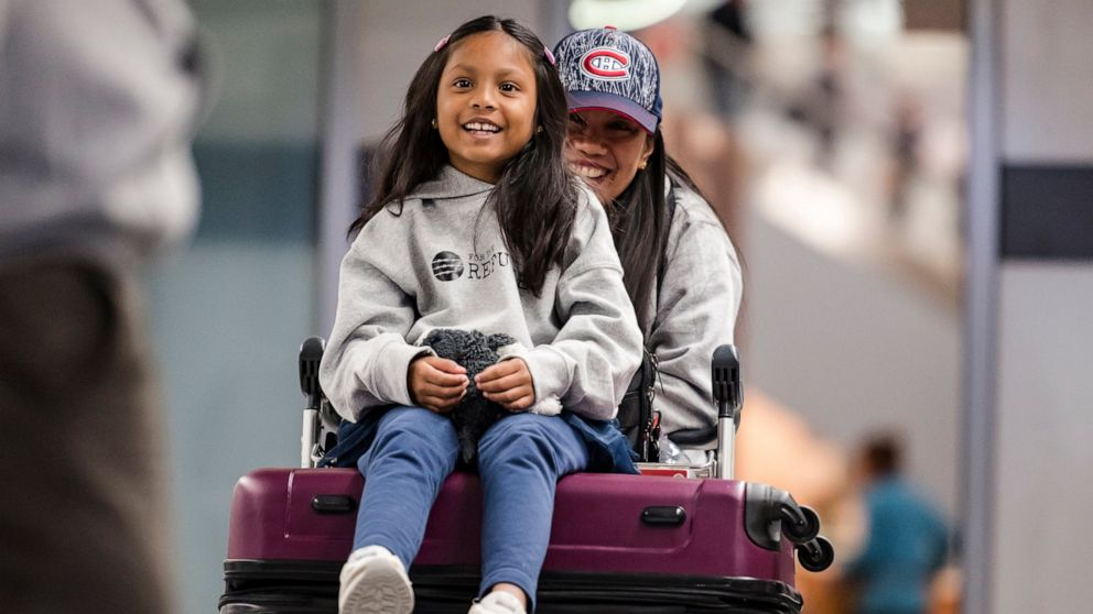 Vanessa Rodel and her 7-year-old daughter Keana exit Lester B. Pearson Airport in Toronto on Monday, March 25, 2019. The Filipino woman who helped shelter former NSA contractor Edward Snowden when he fled to Hong Kong has been granted refugee status in Canada. (Christopher Katsarov/The Canadian Press via AP)