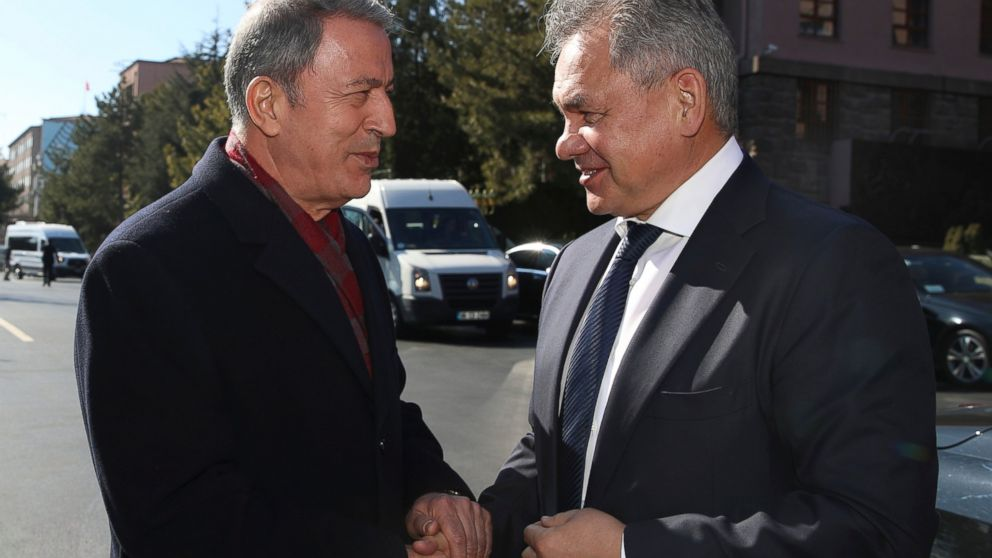 """Turkish Defence Minister Hulusi Akar, left, and Russia's Defence Minister Sergei Shoigu greet each other before their talks in Ankara, Turkey, Monday, Feb. 11, 2019. Shoigu said at the start of Monday's meeting with his Turkish counterpart Akar that the two countries' experts have done """"a lot of work to coordinate on issues related to the stabilization in Idlib and issues related to the east bank of the Euphrates River."""" (Defence Ministry via AP, Pool)"""