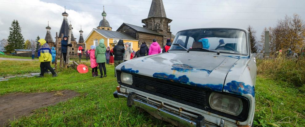 In this photo taken on Oct. 7, 2018, people walk the street with the 18th century Trinity Church in the background in the village of Nyonoksa, northwestern Russia. The Aug. 8, 2019, explosion of a rocket engine at the Russian navys testing range jus