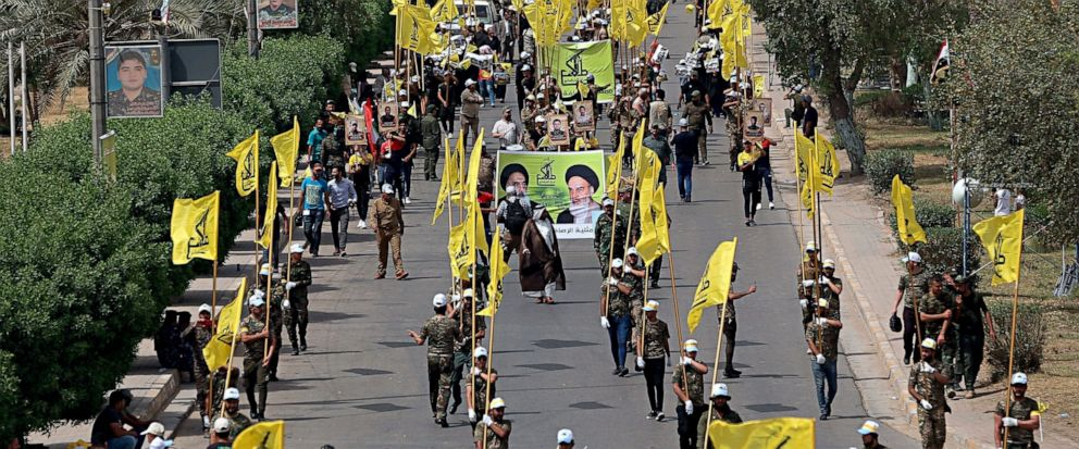 "FILE - In this June 8, 2018 file photo, Iraqi Popular Mobilization Forces march as they hold their flag and posters of Iraqi and Iranian Shiites spiritual leaders during ""al-Quds"" or Jerusalem Day, in Baghdad, Iraq. When U.S. Secretary of State Mike"