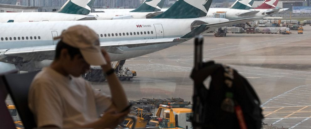 """A man checks his smartphone while Cathay Pacific Airways planes park at the Hong Kong International Airport on Monday, Aug. 12, 2019. The chief executive of Hong Kongs Cathay Pacific Airways said Monday there will be """"disciplinary consequences"""" for"""
