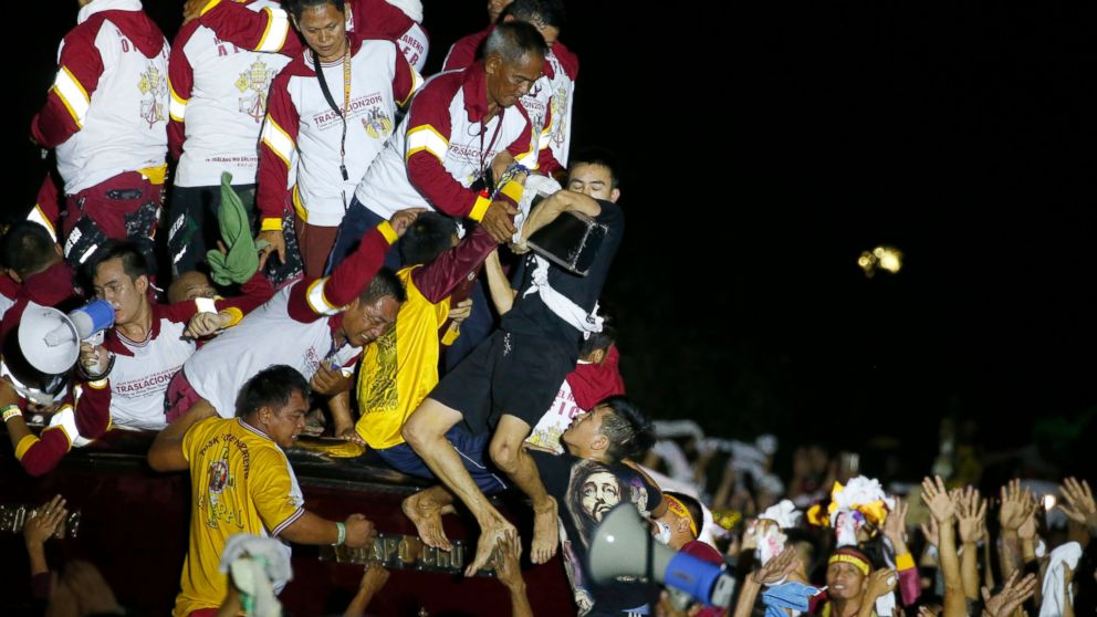 Filipino Roman Catholic devotees jostle to kiss and rub with towels the image of the Black Nazarene in a raucous procession to celebrate its feast day Wednesday, Jan. 9, 2019, in Manila, Philippines. Tens of thousands of mostly barefoot Filipino Catholics joined the annual procession of a centuries-old statue of Jesus Christ to celebrate the Feast of the Black Nazarene which usually ends before dawn the next day. (AP Photo/Bullit Marquez)