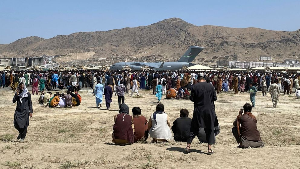 Hundreds of people gather near a U.S. Air Force C-17 transport plane at a perimeter at the international airport in Kabul, Afghanistan, Monday, Aug. 16, 2021. On Monday, the U.S. military and officials focus was on Kabul's airport, where thousands of