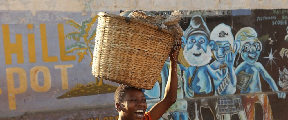 A young boy smiles while carrying a basket to a popular market in Harare, Thursday, Aug, 8, 2019. Many Zimbabweans who cheered the downfall of longtime leader Robert Mugabe two years ago have found the countrys economy even worse than before.(AP Pho