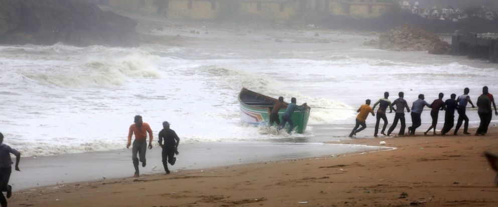 People try to pull back a fishing boat that was carries away by waves on the Arabian Sea coast as others run to take shelter in Veraval, Gujarat, India, Thursday, June 13, 2019. Authorities have evacuated nearly 300,000 people from Indias western co