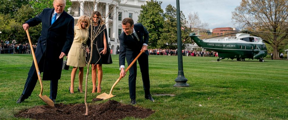 FILE - In this April 23, 2018 file photo, Melania Trump, second right, and Brigitte Macron, second left, watch as President Donald Trump and French President Emmanuel Macron participate in a tree planting ceremony on the South Lawn of the White House