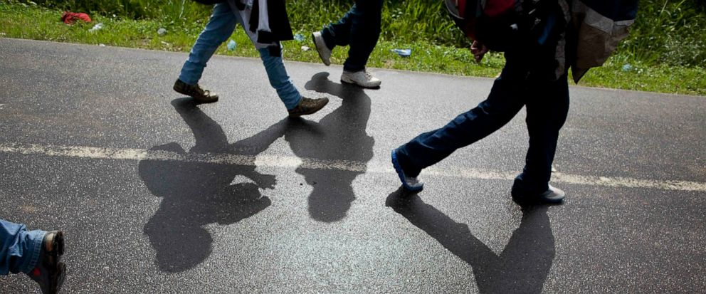 FILE - In this Aug. 14, 2012 file photo, Honduran migrants walk along a road after being deported by bus from Mexico to Corinto, Honduras, near the border with Guatemala. On Sunday, April 14, 2019, Mexican immigration officials said they have sent a