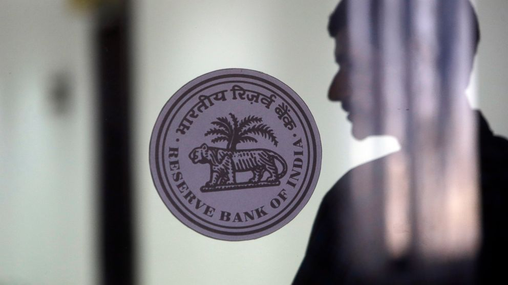 A man walk past a Reserve Bank of India logo at their head office in Mumbai, India, Thursday, Feb. 7, 2019. India's central bank has lowered its key interest rate by a quarter of a percentage point to 6.25 percent, a step that is expected to boost the economy. (AP Photo/Rajanish Kakade)