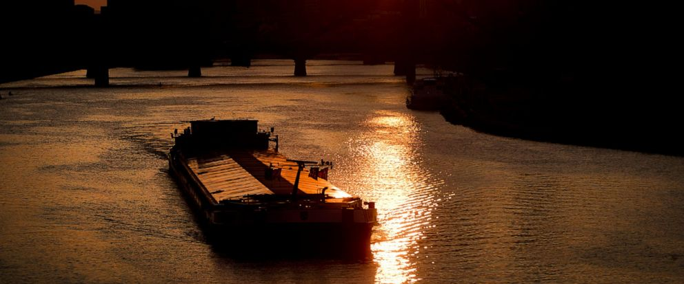 A cargo shop is seen on the river Main as the sun sets behind the bank buildings in Frankfurt, Germany, Monday, April 15, 2019. (AP Photo/Michael Probst)