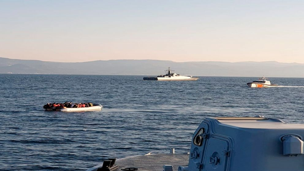 In this photo provided by the Hellenic Coast Guard and taken from a vessel shows a dinghy with migrants, left, with Turkish ships in the background, in the narrow stretch of water between the eastern Greek island of Lesbos and the Turkish coast on Fr