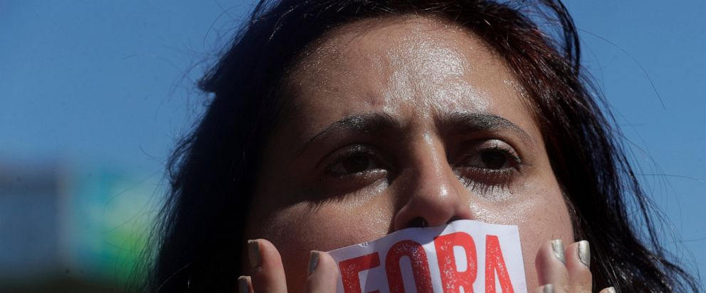 """A teacher covers her mouth with a sticker that reads in Portuguese """"Bolsonaro out!"""" in reference to Brazils President Jair Bolsonaro, during a national strike against cuts in the education budget, in Brasilia, Brazil, Tuesday, Aug. 13, 2019. Union l"""