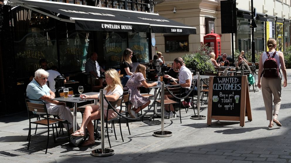 FILE - In this Monday, Aug. 3, 2020 file photo, a sign outside a pub reads: Wanted Customers in central London. The British economy recouped some further lost ground during July after a swath of coronavirus restrictions were lifted, official figure