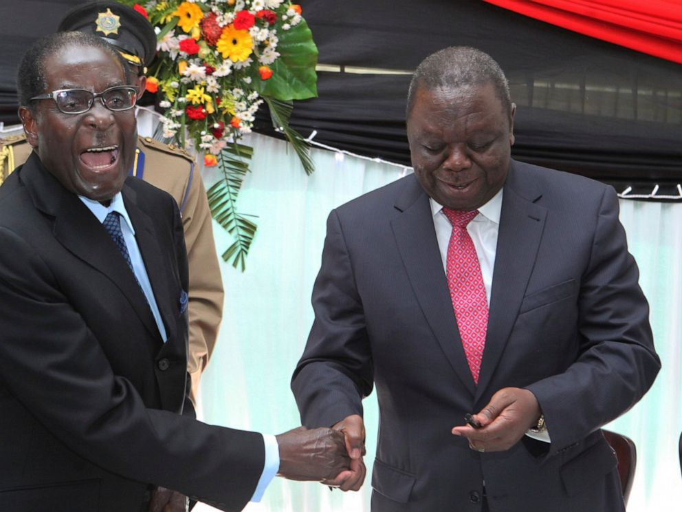 FILE - In this Wednesday, May 22, 2013 file photo Zimbabwean President Robert Mugabe, left, shakes hands with Prime Minister Morgan Tsvangirai after he signed the new constitution into law at State house in Harare. On Friday, Sept. 6, 2019, Zimbabwe