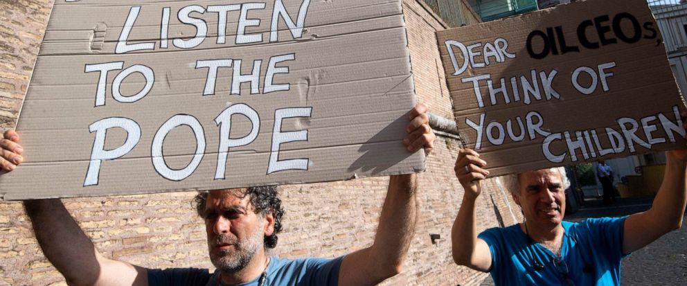Activists hold up signs outside the Vatican as Pope Francis meets with oil executives, Friday, June 14, 2019. The meeting marked the second year that Francis has invited oil and financial sector executives to the Vatican to impress upon them his conc