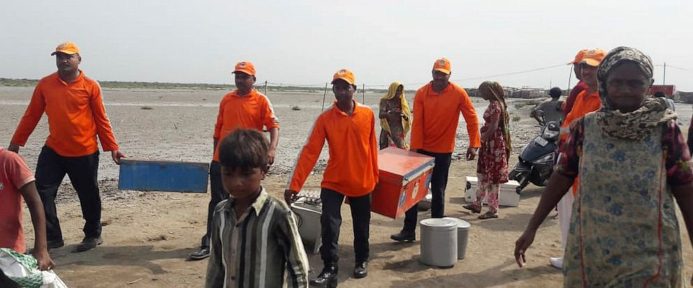 In this photo released by the National Disaster Response Force (NDRF), NDRF soldiers help villagers to evacuate from Naliya village in the western state of Gujarat, India, Wednesday, June 12, 2019. Indian authorities were bracing Wednesday for a seve